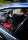 An image of a lady driving her car with her handbag in view